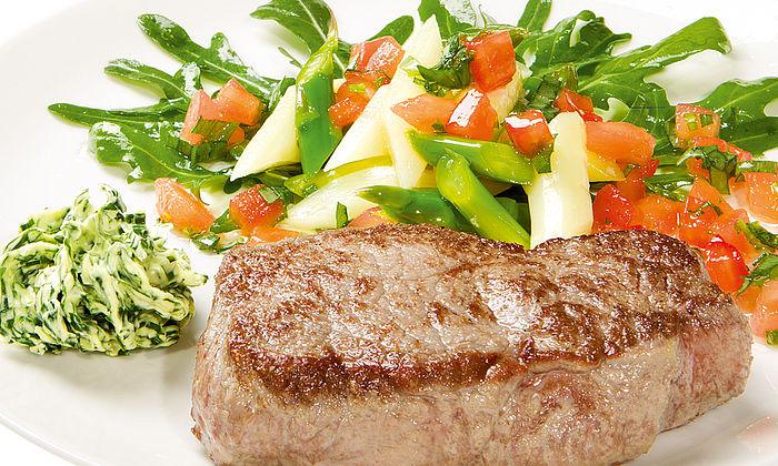 Frisches Rinderrumpsteak mit Bärlauch-Butter und Salat von grünem und weißem Spargel auf Rucola in Tomaten-Estragonvinaigrette